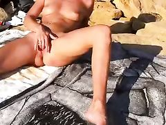 Nudist woman masturbating at the beach